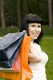 attractive girl holding in hands bags with purchases poster
