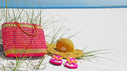 Pretty hat, beach bag, and flip flops on beach