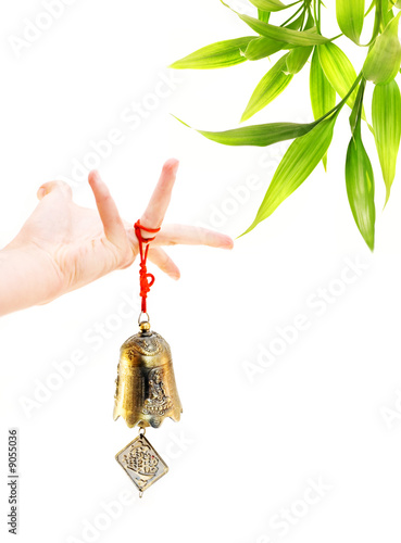Papiers peints Bambou Hand holding golden bell and bamboo plant in the corner