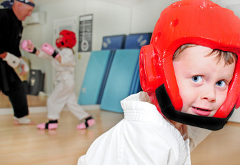 Young boy in karate saftey gear in dojo