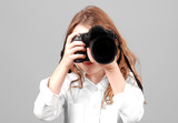 Young girl aiming digital SLR camera poster