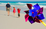 Father and children strolling on beach by colorful pinwheel poster