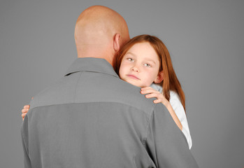 Young girl receiving sweet hug from father