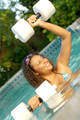 Healthy young woman doing water aerobics