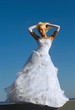 Blonde bride on blue sky background
