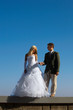Bride and fiance on blue sky background