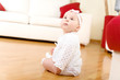 Eight month old baby girl seated on a hardwood floor