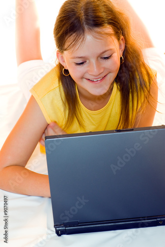 Adorable little girl playing on laptop computer