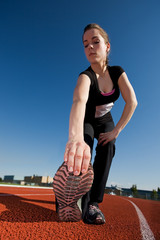A beautiful woman athlete stretching before a race