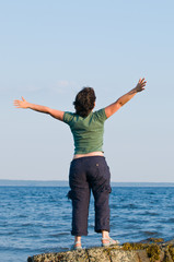 Young woman at the beach standing on rock with arms outstretched