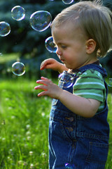 Little boy in a field playing with bubbles