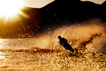 A male waterskiing in the evening sunset