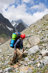 Gril backpacker traveling on talus in mountains