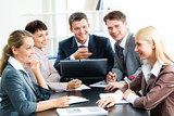 Photo of business group sitting at workplace