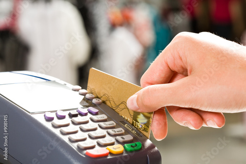 Leinwandbild Motiv Close-up of hand holding plastic card in payment machine