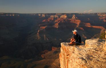 Trekker admiring Grand Canyon at sunset. Arizona. USA