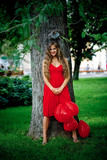 Beautiful woman in red dress staying near tree poster