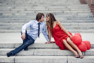 Teen fashion couple kissing sitting on staircase