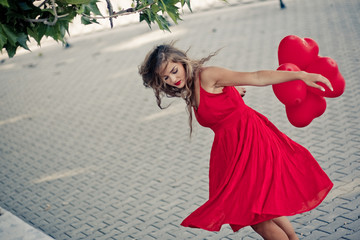 Beautiful girl in red dress moving with ballons as hearts