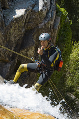 Men descending waterfall in rappel