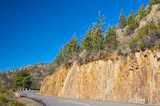 mountain road with sharp curve with blue sky background poster