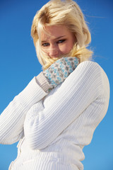 Teenage girl trying to keep herself warm, looking at camera