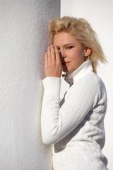 Teenage girl standing beside white pillar