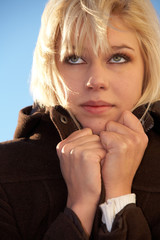 Teenage girl holding coat, looking up, exterior