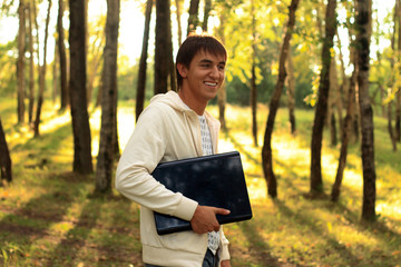 Student walking in park holds laptop
