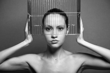 Surrealistic portrait of young woman with cage