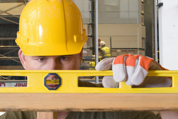 Construction worker using level