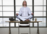 Businesswoman meditating on desk