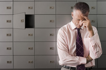 Frustrated businessman in front of open safe