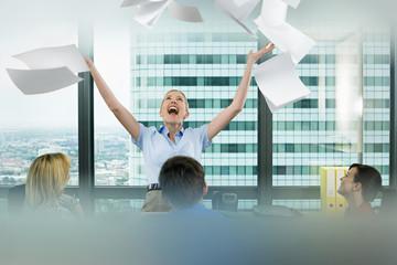 Businesswoman throwing paperwork in meeting
