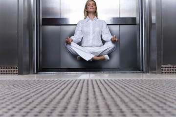 Businesswoman levitating in elevator