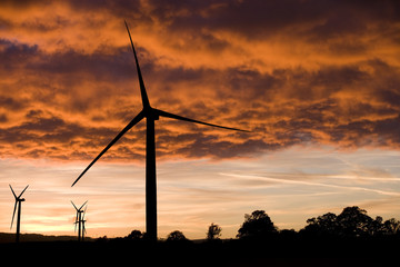 Windmills silhouetted against orange clouds