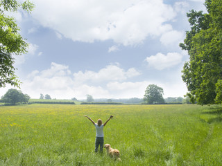 Woman and dog standing in vast field