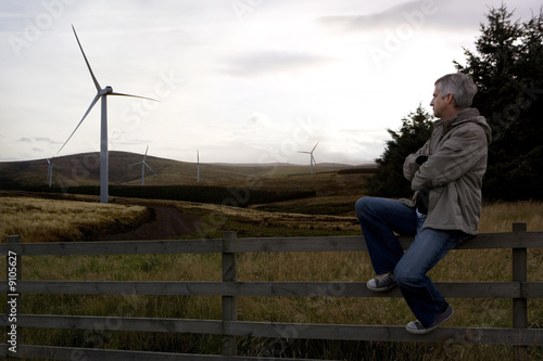 Man overlooking windmill covered landscape