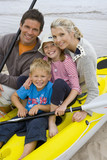 Young family sitting in kayak on beach