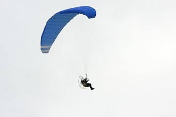 Motor powered paraglider isolated on gray sky