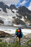 Backpacker girl in helmet climbing on high mountain poster