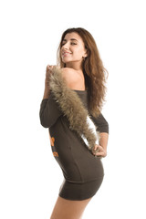 Lovely brunette in sexy dress posing with fur in her hands