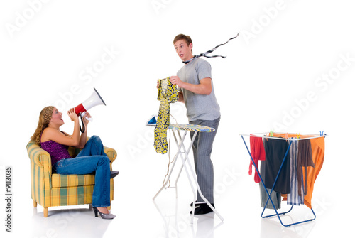 Young bossy woman shouting with megaphone to husband