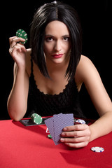 Determined attractive brunette playing cards at a red poker