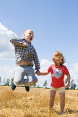 little girl and boy jumping high on a sunny day