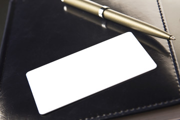 White business card and pen lays on organizer with a black cover