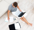 Busy young man sitting on floor and using a laptop