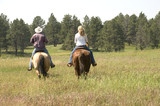 Two People Riding Horses on Wyoming Ranch poster