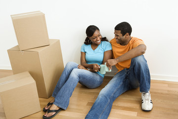 Black couple with moving boxes.