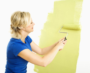 Woman painting wall.